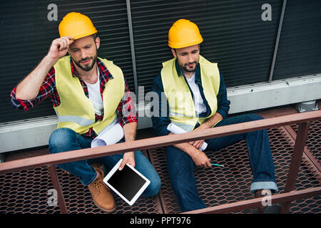 architects with blueprints and digital tablet sitting on construction - Stock Photo