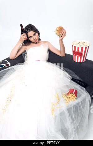 depressed young bride in wedding dress sitting on couch with beer and junk food on white - Stock Photo