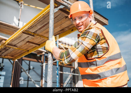 handsome builder climbing on scaffolding at construction site and looking at camera - Stock Photo
