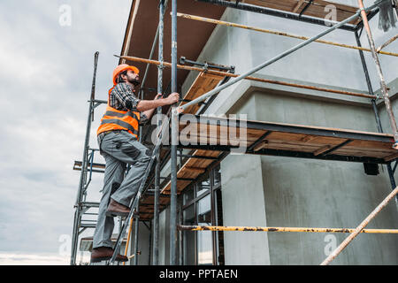 handsome builder climbing on scaffolding at construction site - Stock Photo