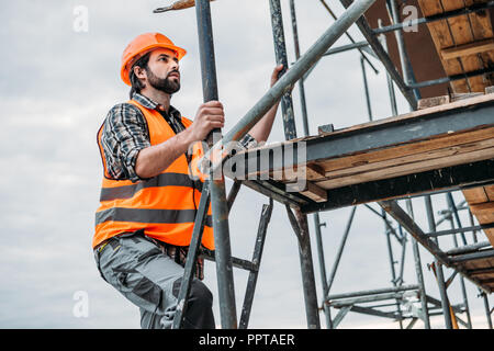 bearded builder climbing on scaffolding at construction site - Stock Photo