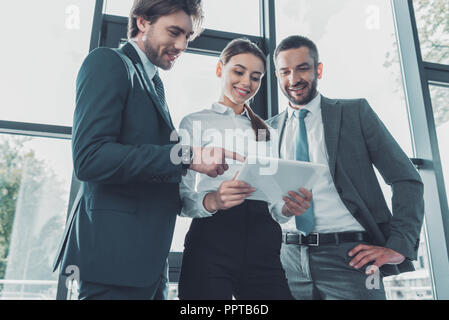 bottom view of happy business people using tablet together at modern office - Stock Photo