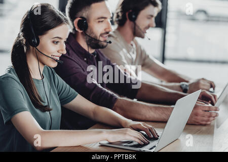 happy team of call center managers working together while sitting in row at modern office - Stock Photo