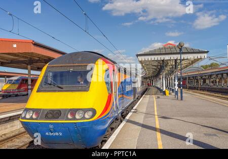 Typical view of a train preparing to depart at a railway station platform. A 19th Century canopy is on one side and a blue sky is above. - Stock Photo