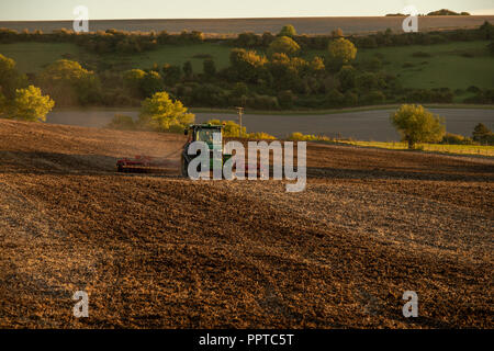 Farmer ploughing a field in the village of Edington in Wiltshire UK - Stock Photo