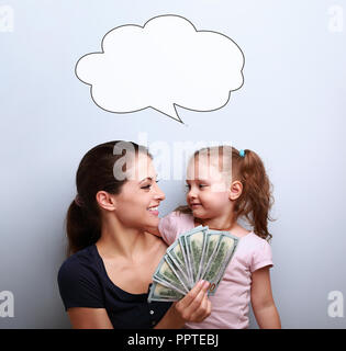 Smiling mother and happy daughter hugging, looking each other, holding dollars and thinking how to spend it. Happy winning family on blue background - Stock Photo