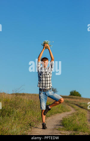 beautiful young man doing yoga on the road on a Sunny day. - Stock Photo