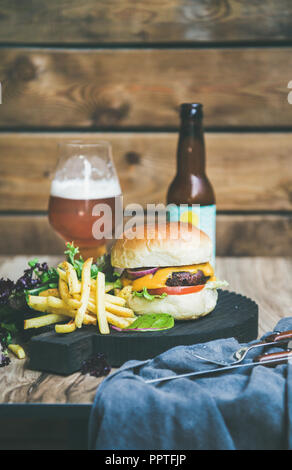 Classic burger dinner with beer and french fries - Stock Photo