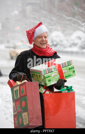 Joyful Mature Man Bearing Christmas Presents on a Snowy New York City Street, USA - Stock Photo
