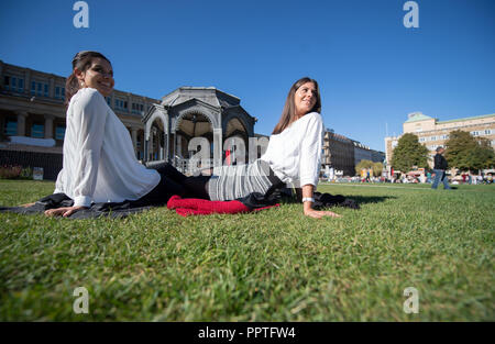 27 September 2018, Baden-Wuerttemberg, Stuttgart: Sarah (L) and Anne sit on a meadow in front of the music pavilion on the Schlossplatz. Photo: Marijan Murat/dpa - Stock Photo
