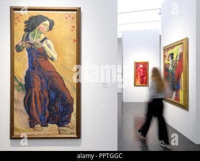 27 September 2018, Baden-Wuerttemberg, Stuttgart: A visitor of the preview of the exhibition entitled 'Ecstasy' in the Kunstmuseum Stuttgart passes by a work by Ferdinand Hodler from 1911 entitled 'Enchanted Woman'. The exhibition and ecstasy traces the state of 'being outside oneself' with around 250 works from antiquity to the present day. The works of art can be seen until 24 February 2019. Photo: Bernd Weißbrod/dpa - Stock Photo