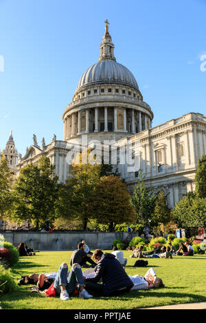 St Paul's, London, 27th Sep 2018. People enjoy the beautiful autumn sunshine with warm temperatures and blue skies, many relax on the lawns around St Paul's Cathedral in the City of London. Credit: Imageplotter News and Sports/Alamy Live News - Stock Photo