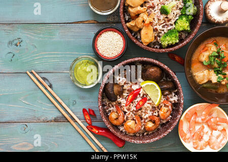 Asian food. Shrimp, rice, mushrooms, broccoli, stewed chicken, sauces on a rustic wooden background. Top view, space for text - Stock Photo