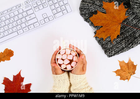 Coffee with marshmallow in hands on a white desktop next to an empty block and keyboard, autumn leaves. Fall mood. Top view, flat layout. Copy the spa - Stock Photo