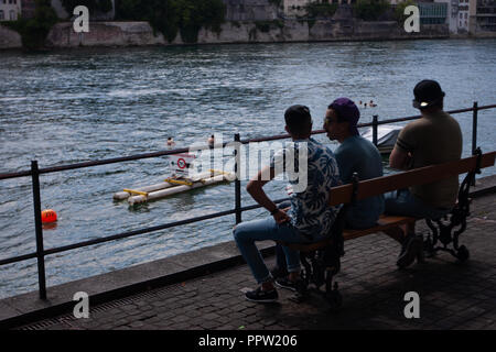 People sitting at the river Rhine in Basel - Stock Photo