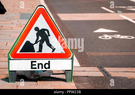 End of Road Works sign next to a Cycle lane - Stock Photo