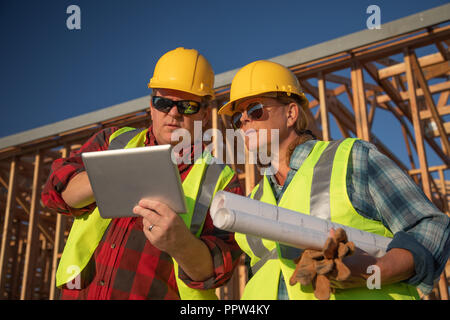 Male and Female Construction Workers Using Computer Pad at Construction Site. - Stock Photo
