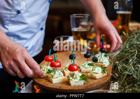 Delicious snacks for beer. Fresh canapes with tomatoes, olives, greens on white bread on the table. - Stock Photo