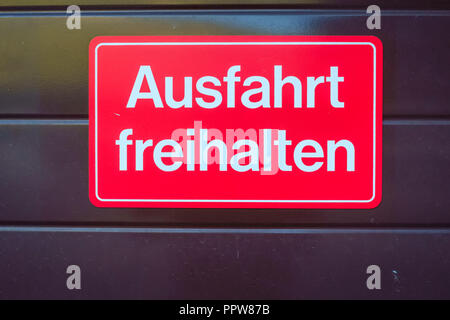 Red traffic sign in the city of Lauterbrunnen (Berner Oberland, Switzerland) indicating to keep the exit free. - Stock Photo