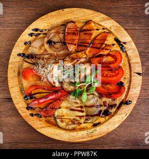 Chopped vegetables: peppers, mushrooms, zucchini and onions on the board - Stock Photo