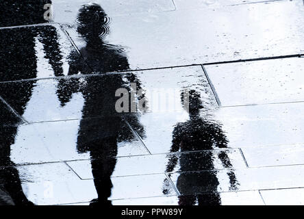 Blurry reflection shadow silhouette in a puddle of siblings and a parent walking wet city street - Stock Photo