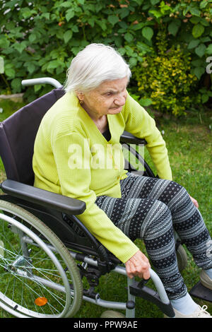 Old lady sitting in wheelchair suffering from dementia spending time outdoor - Stock Photo