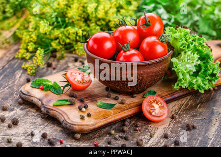 Tomato in a plate on a green background. Mint on the board. A bunch of salad on a board near tomatoes - Stock Photo