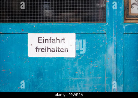 White traffic sign against a blue door in the city of Thun (Berner Oberland, Switzerland) indicating to keep the exit free. - Stock Photo