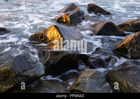 Tide swirling around rocks on the beach in early morning during the golden hour. - Stock Photo