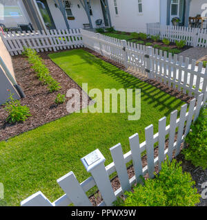 White fence around a sunlit landscaped yard - Stock Photo
