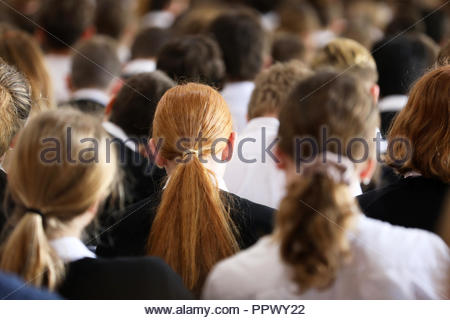 Crowd of high school students in uniform at assembly listening and facing forward. Red haired long hair female girl student in focus. - Stock Photo