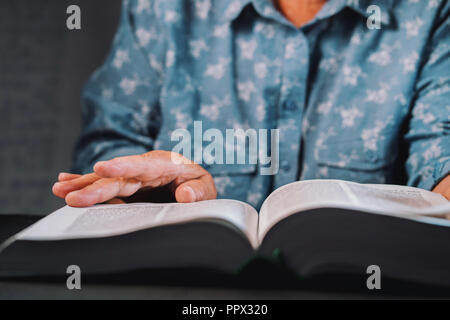 Old woman flipping through pages of book. Grandmother with Bible. Concentrated elderly pensioner with wrinkles on hands looking for information in the library - Stock Photo