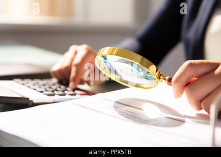 Close-up Of A Businesswoman's Hand Examining Invoice Through Magnifying Glass - Stock Photo