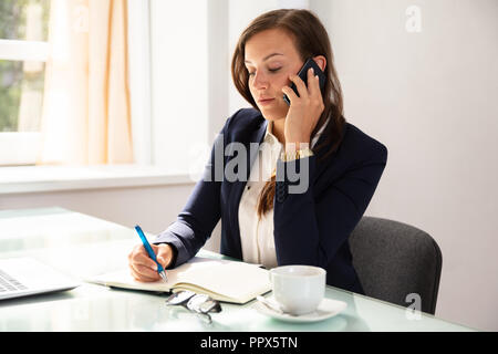 Businesswoman Talking On Cellphone While Writing Schedule In Diary - Stock Photo