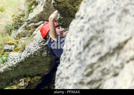 Image of young woman in red helmet climbing on rock - Stock Photo