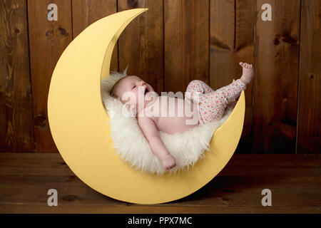 Studio portrait of a yawning, one month old baby girl lying on a moon shaped posing prop. - Stock Photo