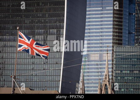 Seen from the south bank of the river Thames, a Union Jack flag flies on the bow of WW2 battleship HMS Belfast with the City of London - the capital's financial centre (aka The Square Mile) in the background, on 27th September 2018, in London, England. - Stock Photo