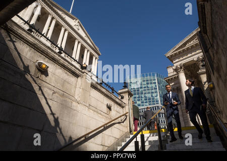 Businessmen descend the steps leading down into Bank Underground station, beneath the Bank of England and neo-classical pillars of Royal Exchange in the City of London - the capital's financial centre (aka The Square Mile), on 27th September 2018, in London, England. - Stock Photo