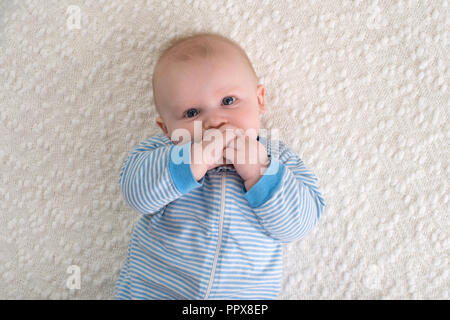 A 2 month old baby boy lying on his back on a white blanket. He is wearing blue and white striped pajamas and has his hand in his mouth and is looking - Stock Photo
