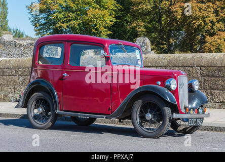 Red Austin Seven (Austin 7) vintage saloon car from 1938 parked by the roadside in the UK. - Stock Photo