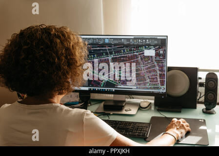 Architect female drawing with cad software designing building. Rear view. She is holding a mobile phone - Stock Photo