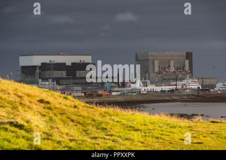 Heysham Lancashire 27th September 2018  Heysham Power Station sitting in the shade with bright sunlight bouncing of the grass on Heysham Barrows Credit: Photographing_North/Alamy Live News - Stock Photo