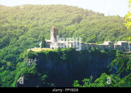 View of Castellfollit de la Roca, medieval Catalan hamlet on cliff in summer day - Stock Photo