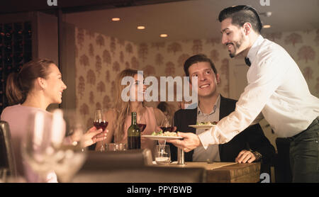 Polite young waiter bringing ordered dishes to guests at restaurant - Stock Photo