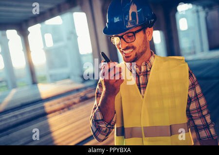 Male architect communicating on walkie-talkie at site - Stock Photo