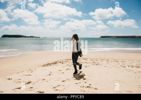 A young girl runs along the beach next to the Atlantic Ocean in Portugal and is happy. - Stock Photo
