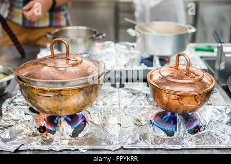 Two bronze, vintage pots on gas stove in restaurant's kitchen - Stock Photo