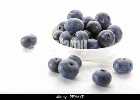 Close up of a white bowl with juicy blueberries on a white tablecloth with some blueberrie scattered on the table - Stock Photo