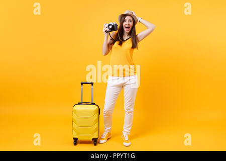 Excited tourist woman in summer casual clothes, hat with suitcase, retro vintage photo camera isolated on yellow background. Female traveling abroad t - Stock Photo