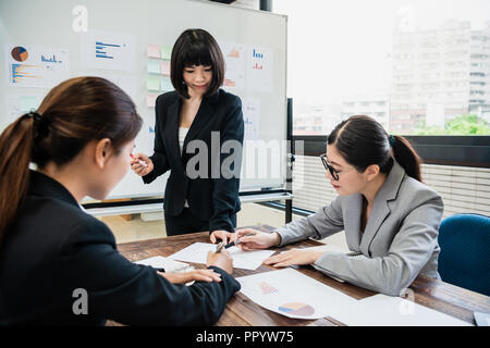 three businesswomen are pointing at the same paper and discussing the new project in the boardroom. Group of business people working together. - Stock Photo